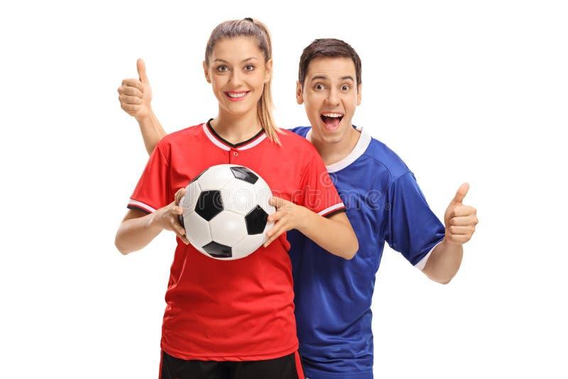 举行橄榄球和男性足球运动员hol的女性足球运动员 免版税库存图片