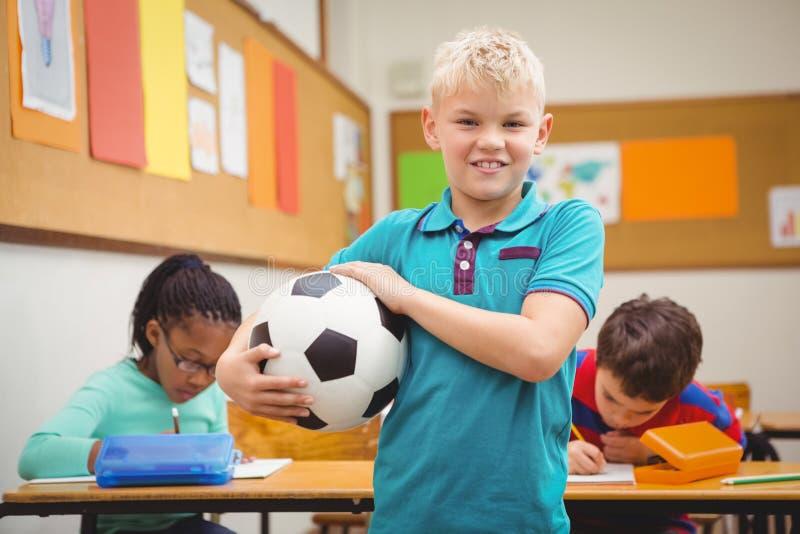 举行橄榄球的微笑的学生 免版税库存图片