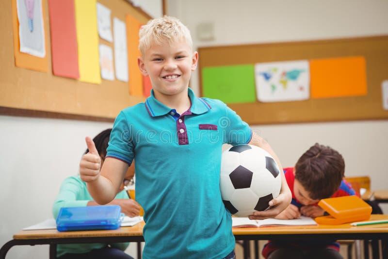 举行橄榄球的微笑的学生 库存照片