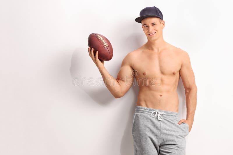 举行橄榄球的英俊的年轻人 免版税库存照片