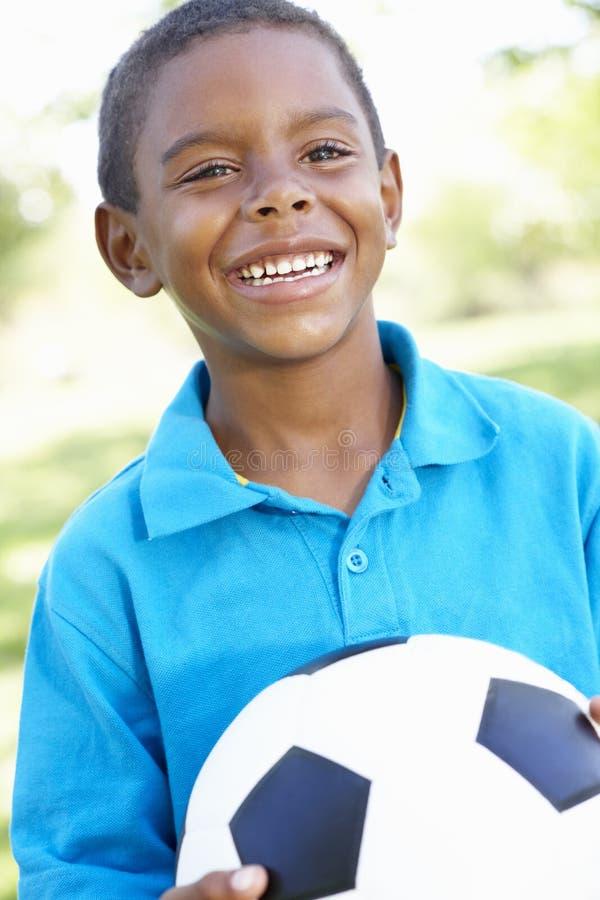 举行橄榄球的年轻非裔美国人的男孩在公园 库存照片