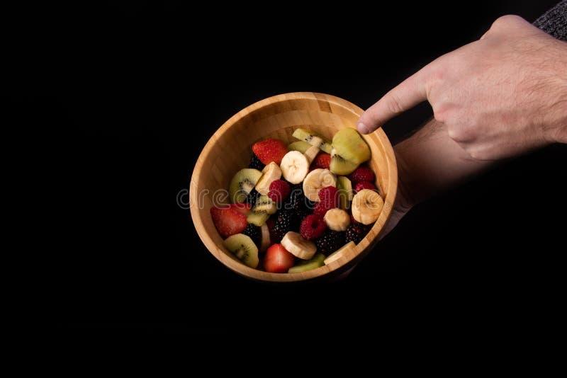 举行水果沙拉碗立即可食非常健康和指点的手 免版税库存图片