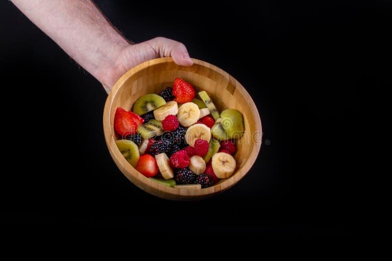 举行水果沙拉碗立即可食非常健康的手 库存图片