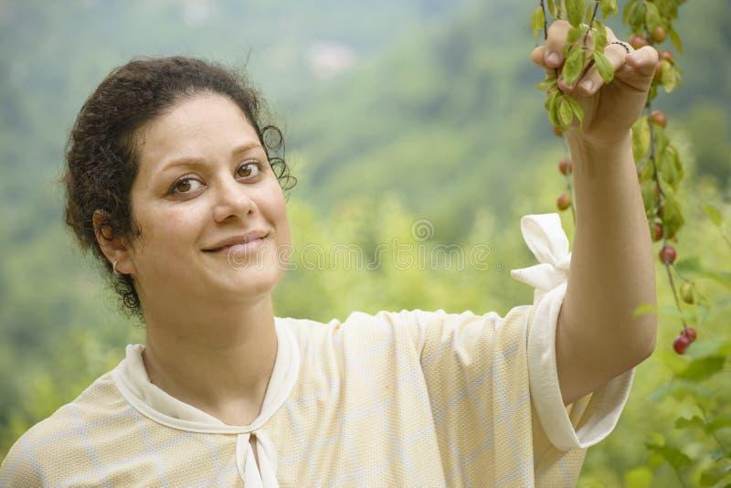 举行洋李分支农业概念的一愉快的年轻女人的画象 图库摄影