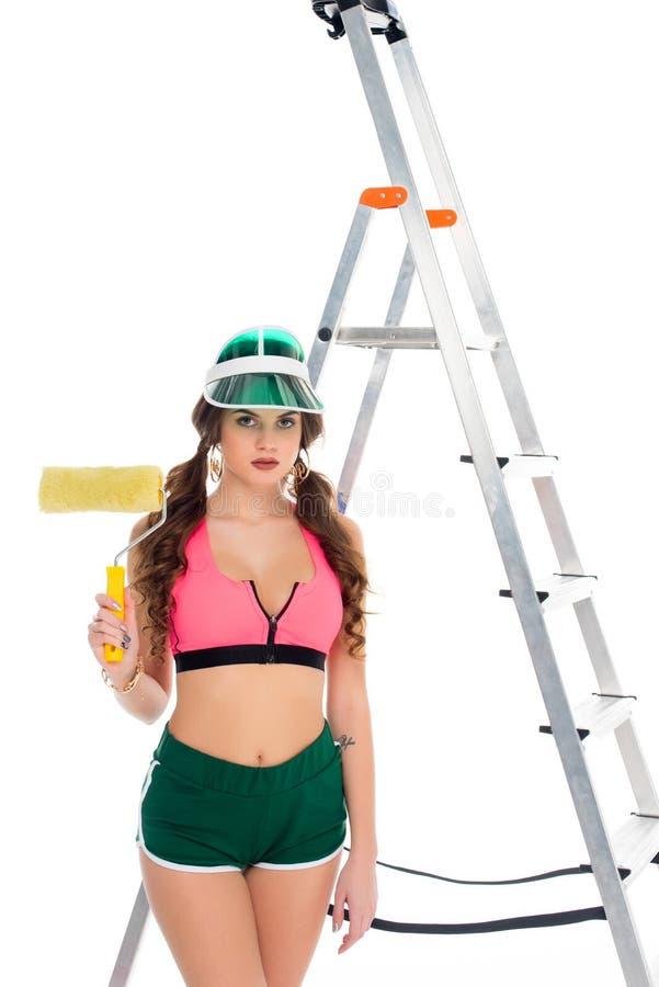 举行漆滚筒和身分的遮阳的可爱的女孩在梯子附近, 库存图片