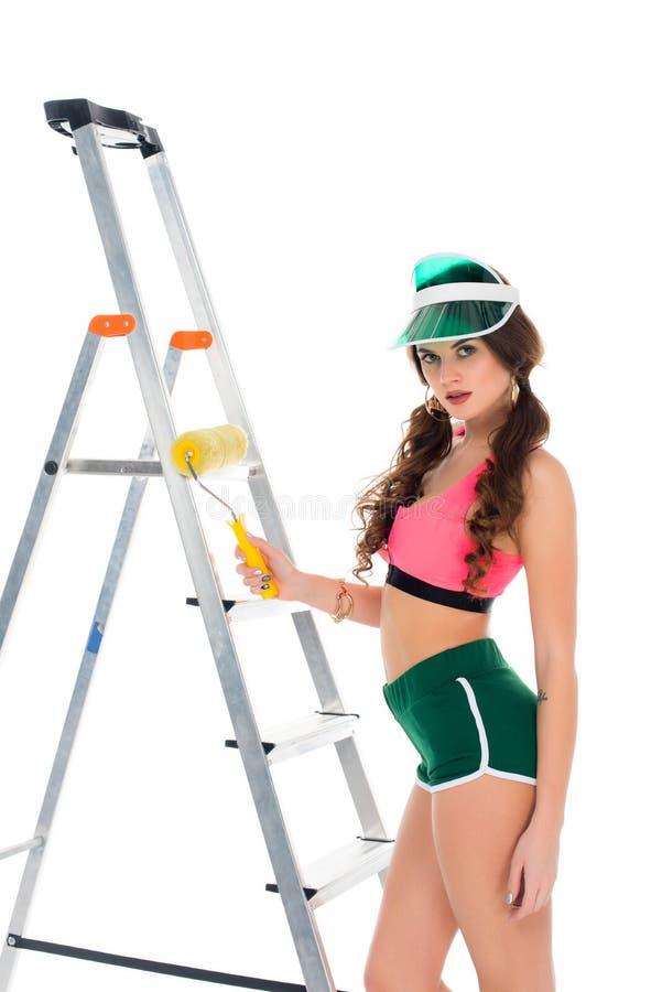 举行漆滚筒和身分的遮阳的性感的女孩在梯子附近, 免版税库存照片