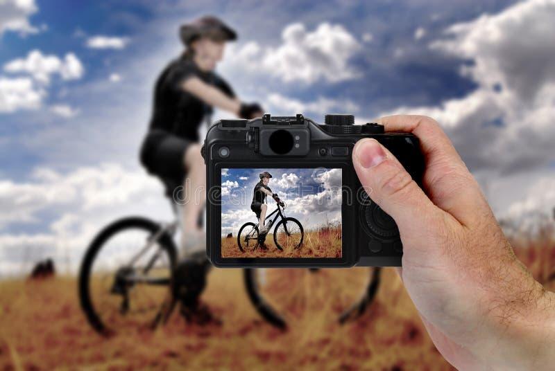 举行照相机摄影山骑自行车的手 库存照片