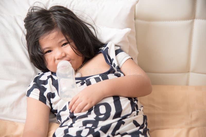 举行牛奶瓶和喝的可爱的女婴 图库摄影