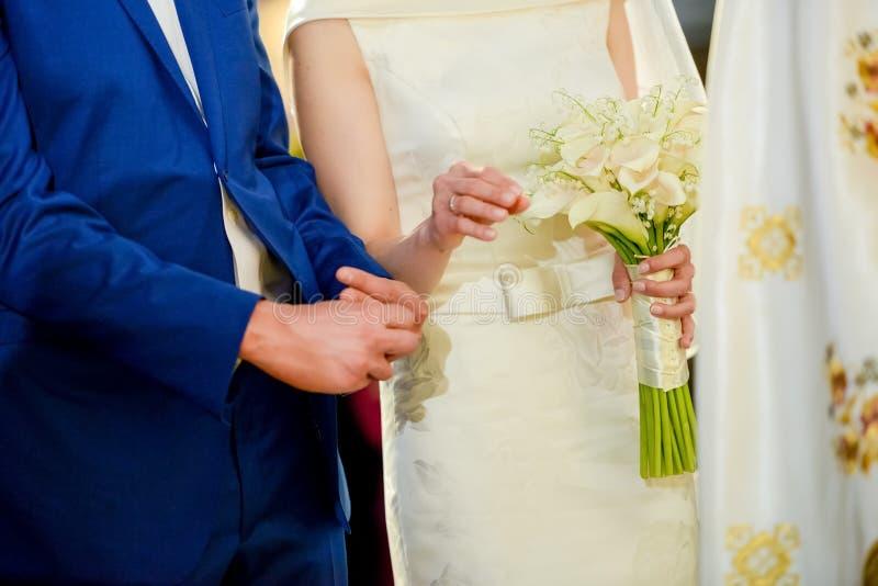 举行由新娘的婚礼花束在她的新郎旁边 库存照片