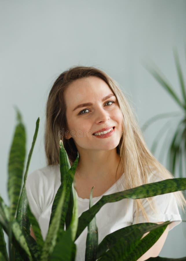 举行盆的植物百合科植物和微笑对照相机的美丽的年轻女人隔绝在灰色 库存图片