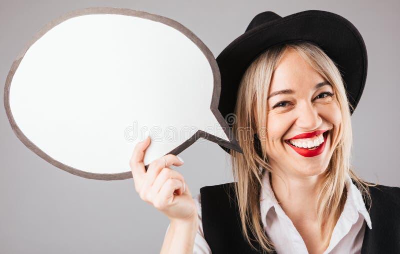 举行空白的横幅讲话的帽子的微笑的愉快的妇女buble为您的文本 灰色背景 库存照片