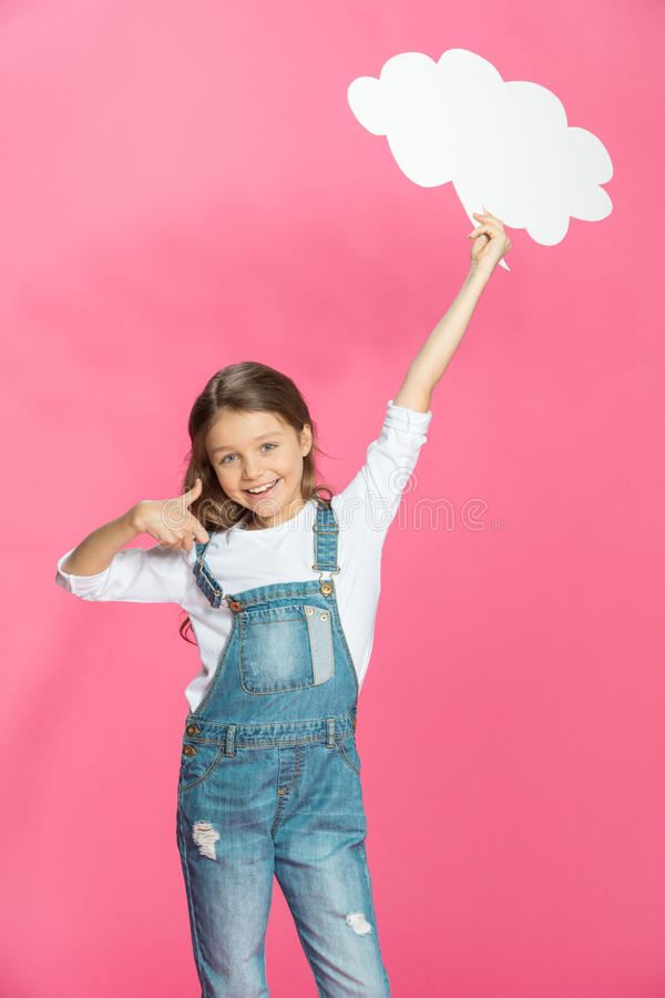 举行空白的讲话的微笑的小女孩起泡和显示赞许 免版税库存照片