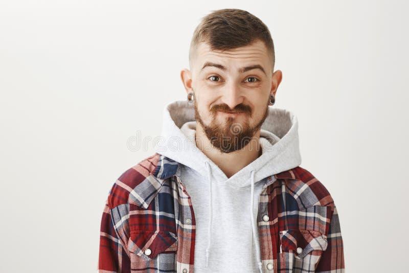 举行笑不感到羞耻朋友 有骨肉的无忧无虑的可爱的行家在耳朵挖洞,微笑,举眼眉 库存图片