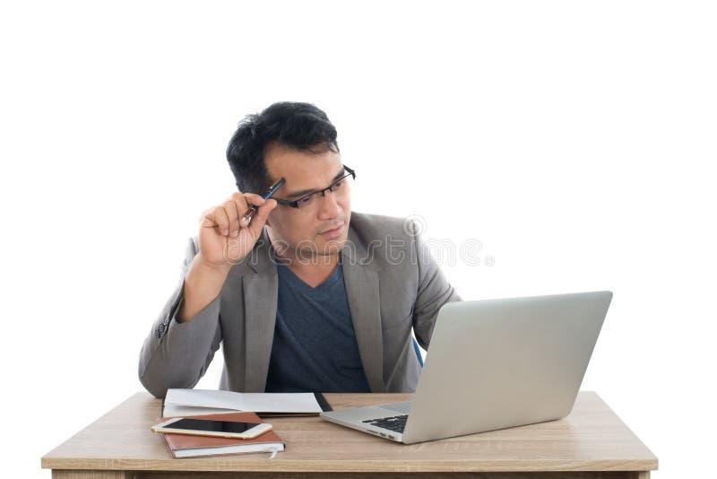 举行笔想法的坐的商人在他的书桌后面喂 免版税库存照片