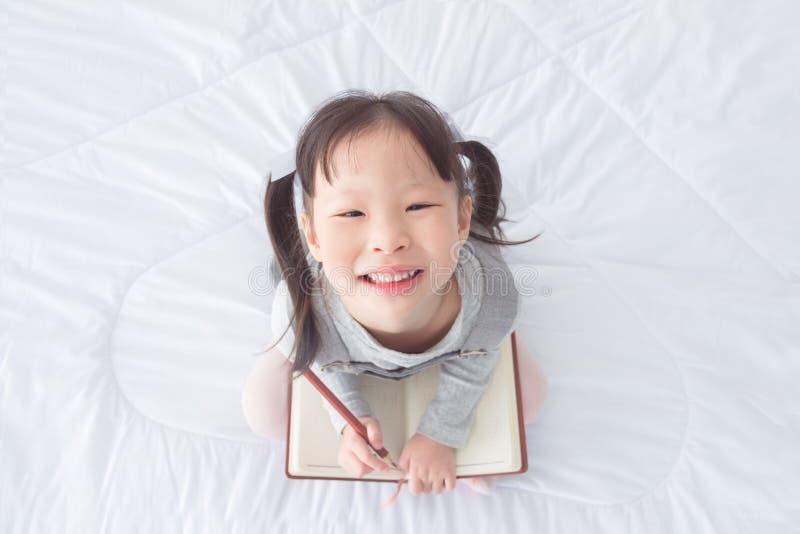 举行笔记本和微笑在床上的小女孩 免版税库存图片