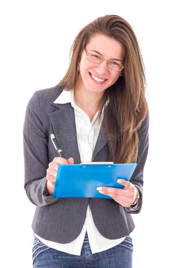 举行笔记本和微笑的愉快的聪明的学生女孩 免版税库存图片