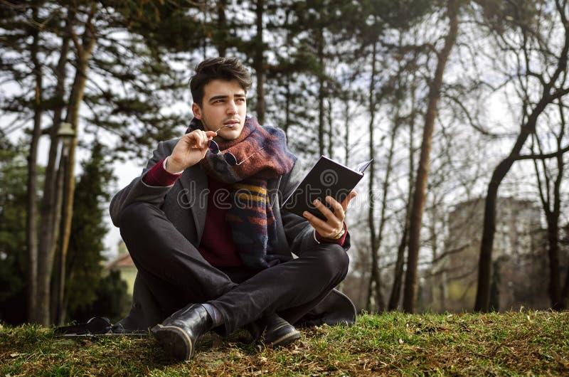 举行笔记本和认为的时髦的男学生 坐草在公园 库存照片