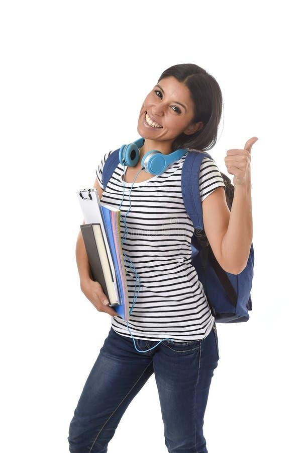 举行笔记薄文件夹和书运载的背包微笑的时髦拉丁学生女孩愉快 免版税库存照片