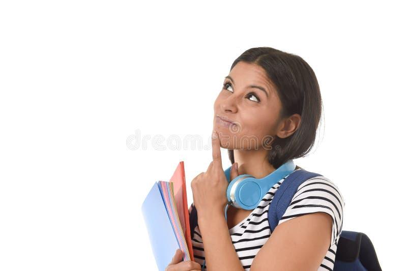 举行笔记薄文件夹和书运载的背包认为的年轻美丽和时髦拉丁学生女孩愉快 库存图片