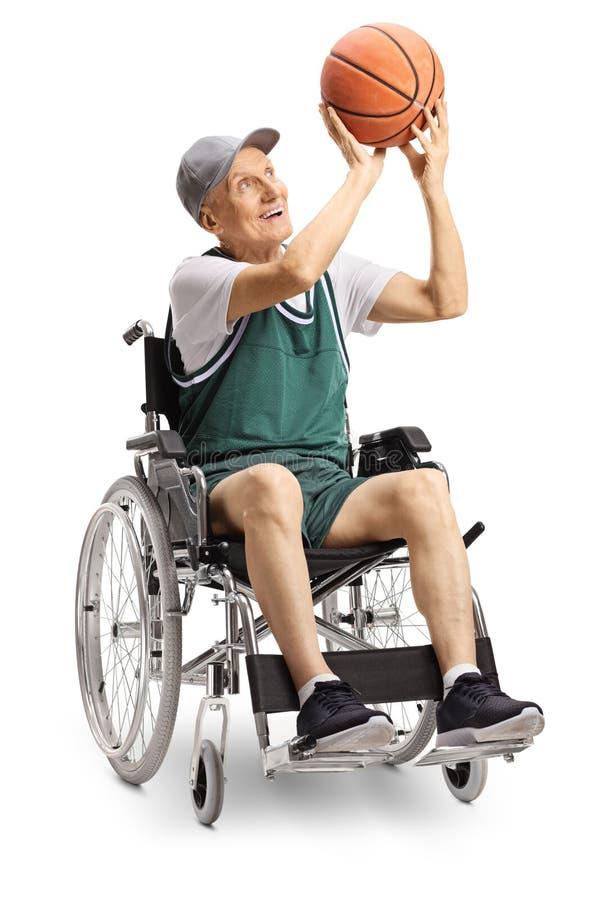 举行篮球和坐在轮椅的资深废人 库存图片
