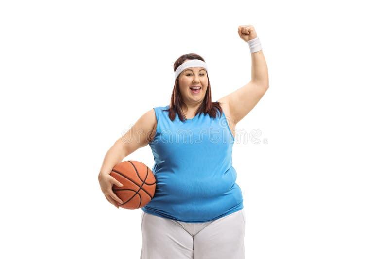 举行篮球和打手势幸福的肥头大耳的妇女 免版税图库摄影