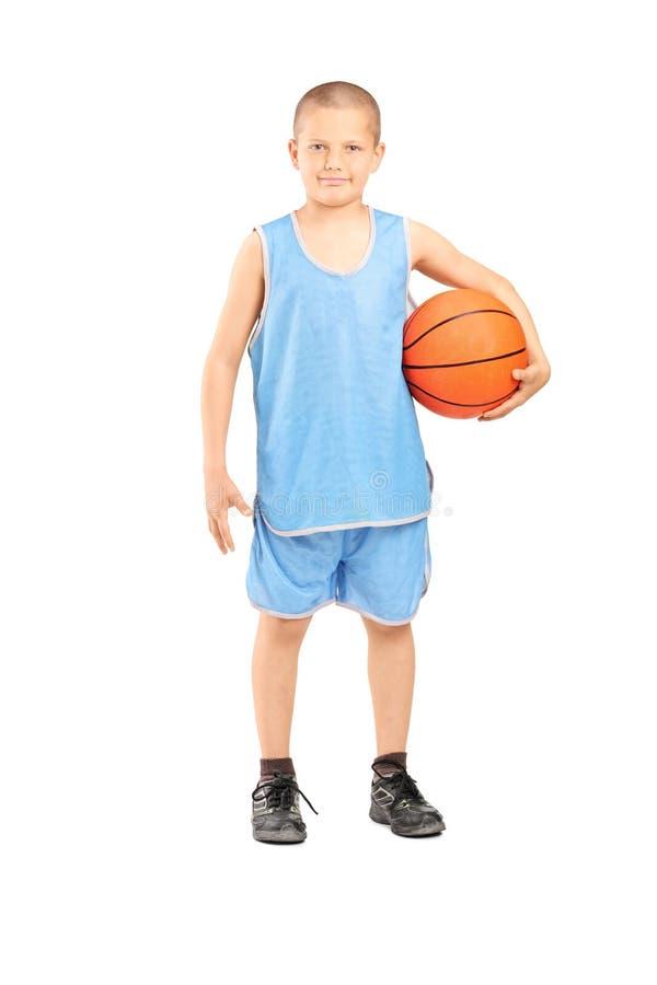 举行篮球的一件蓝色球衣的小男孩 免版税库存图片