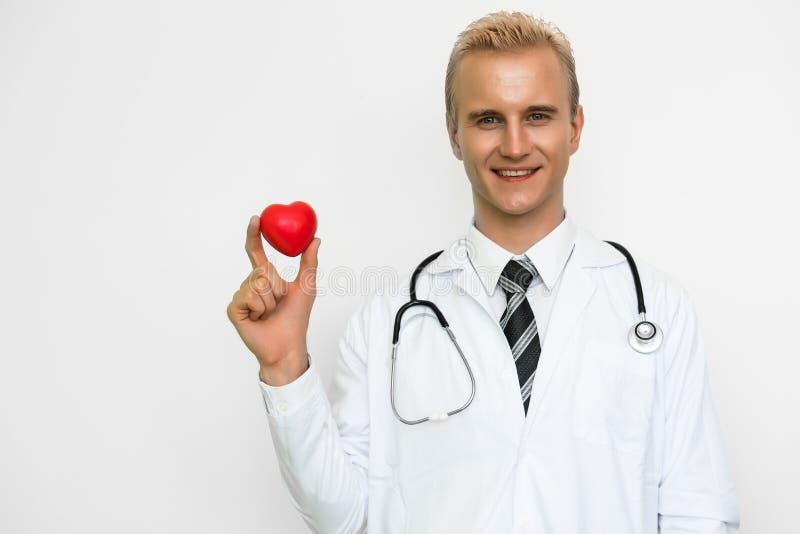 举行红心和微笑的英俊的男性医生 E 幸福人和生活方式题材 库存照片