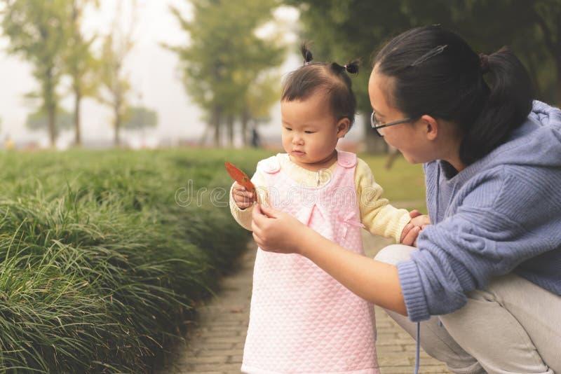 举行红色叶子感觉秋天来的小女儿 免版税库存照片
