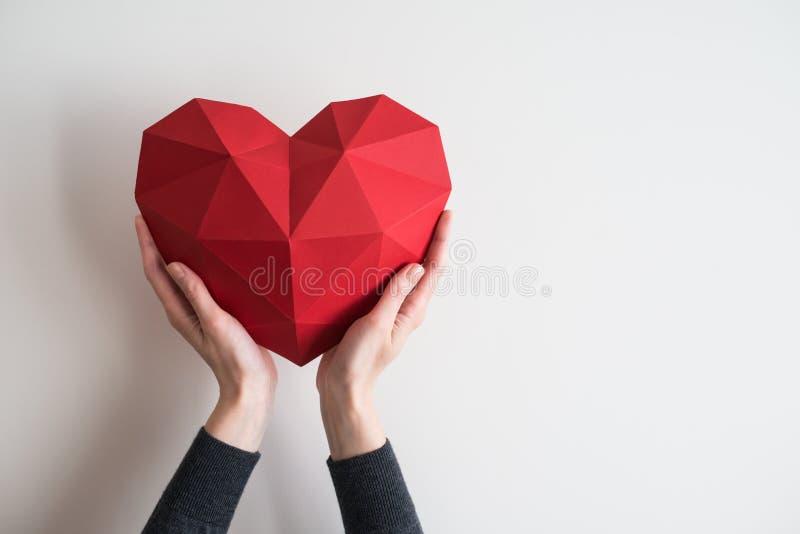 举行红色多角形心脏形状的女性手 库存图片