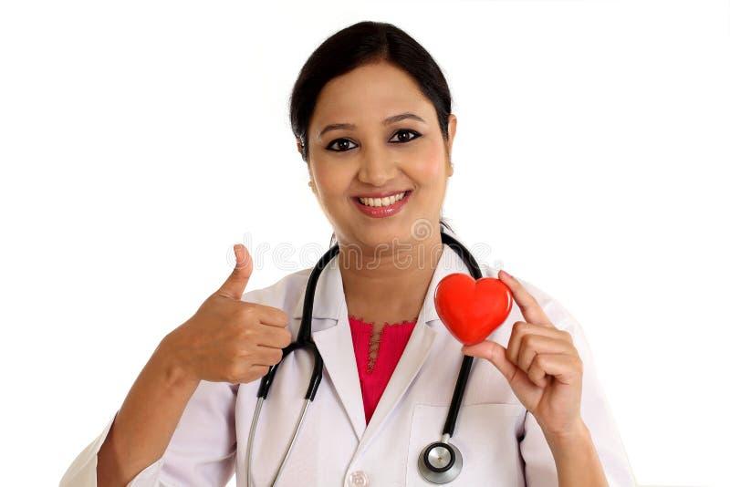 举行红色心脏形状的愉快的年轻女性医生 免版税库存照片