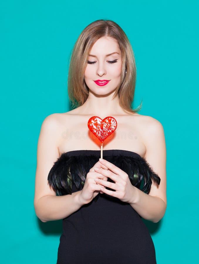 Download 举行红色糖果心脏和神色的时兴的美丽的女孩在他的 在绿色背景的一件黑礼服在演播室 Fashio 库存图片 - 图片 包括有 红色, 背包: 62538877