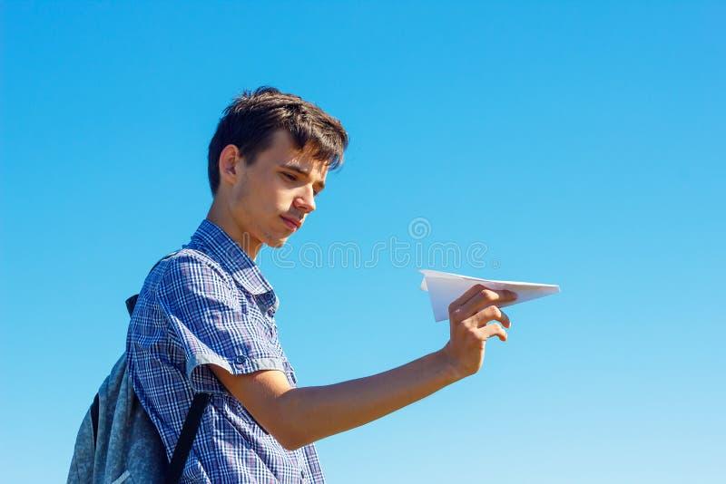 举行纸飞机、飞行的概念和旅行的天空蔚蓝的一年轻人 免版税图库摄影