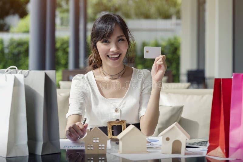 举行网络购物的愉快的亚裔妇女白色信用卡大模型付款,代表销售家不动产购买 图库摄影