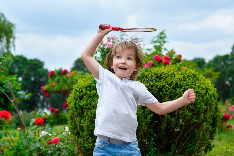 举行羽毛球的愉快的小男孩画象  免版税图库摄影