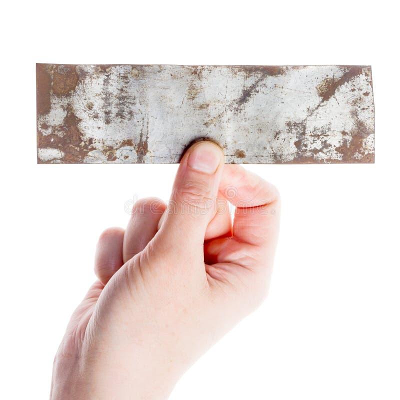 举行老金属片的手 免版税库存照片