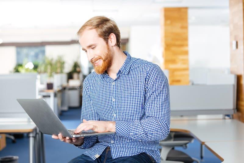 举行膝上型计算机和键入的快乐的商人 库存照片