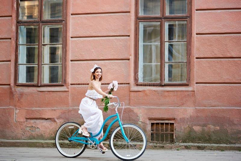 举行花和乘坐的白色礼服的微笑的可爱的女孩自行车下来美丽的老街道 免版税图库摄影