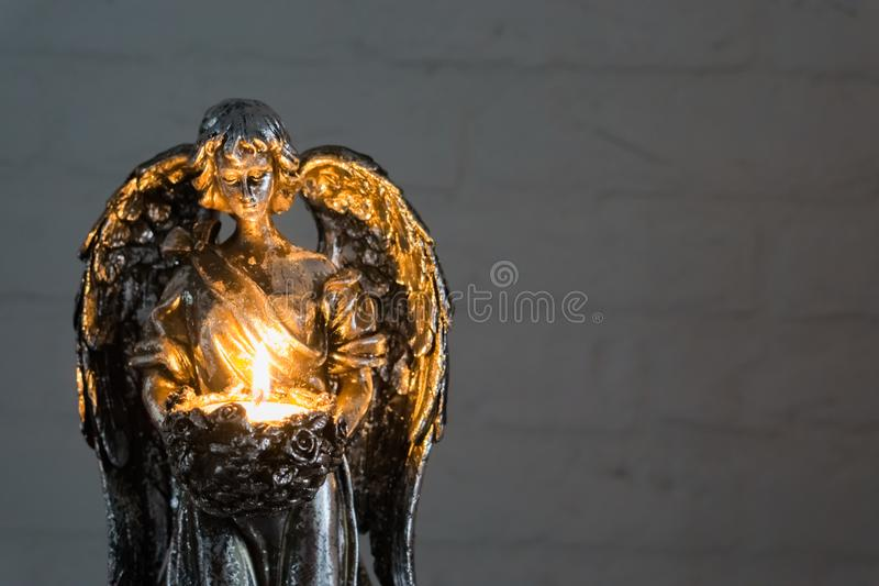 举行被点燃的蜡烛、圣诞节和精神传统的一个银色天使雕象的特写镜头 库存图片