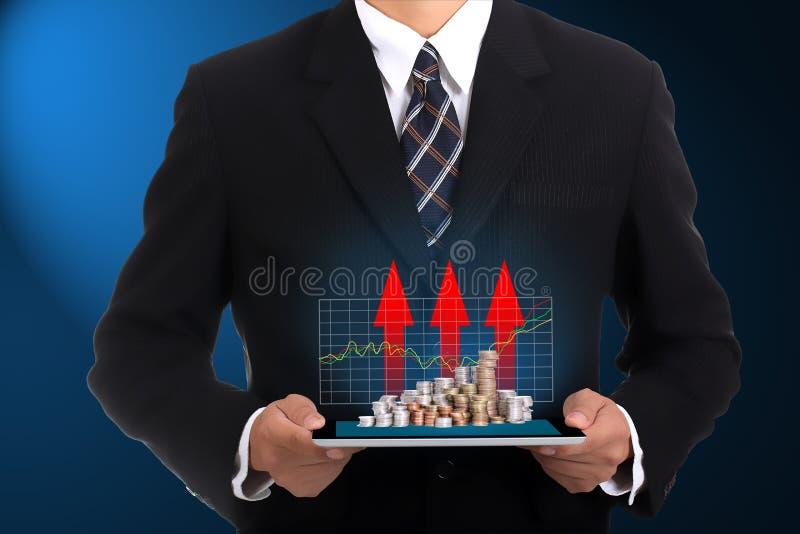 举行触摸板和生长财务的商人 免版税图库摄影