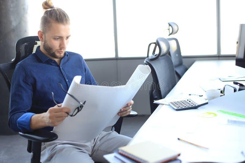 举行计划的射击一位可爱的男性建筑师,当坐在他的办公室时 图库摄影