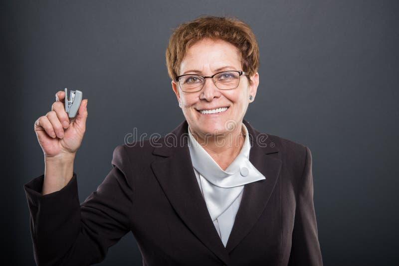 举行订书机和微笑的企业资深夫人 库存图片