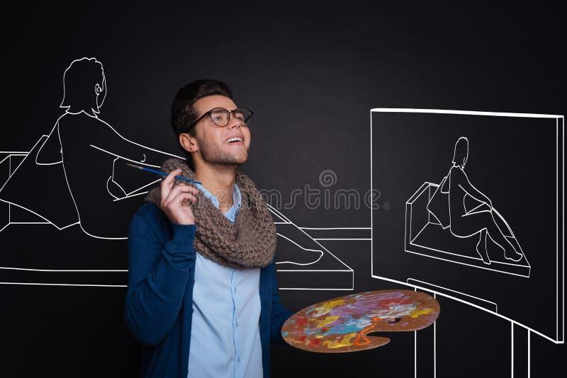 举行调色板和绘的被启发的英俊的人 免版税库存照片