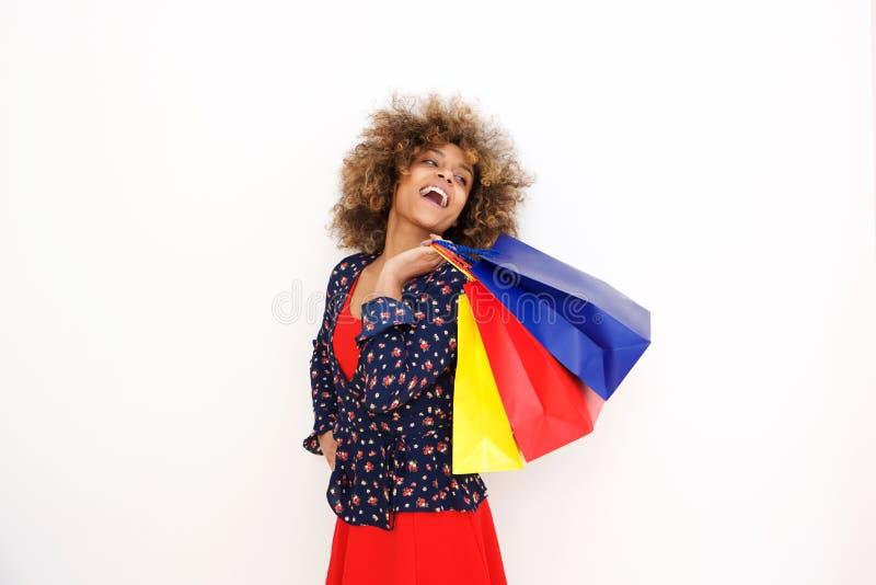 举行购物袋和笑的微笑的年轻非裔美国人的妇女 免版税库存图片