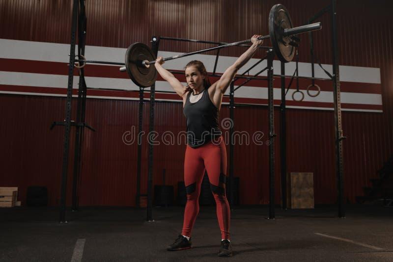 举行重的杠铃天花板的年轻坚强的妇女 做crossfit锻炼的体育妇女 库存照片