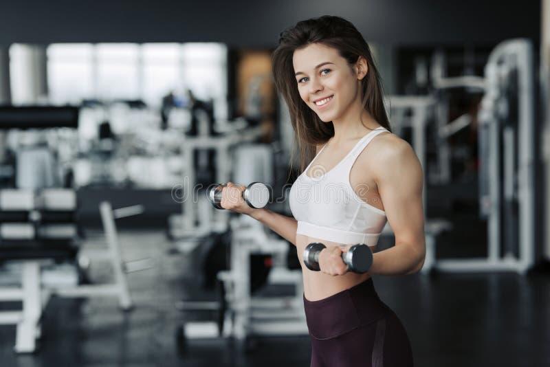 举行重量哑铃的体育衣裳的年轻可爱的妇女做在健身房的健身锻炼 免版税图库摄影