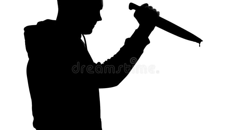 举行锋利的血淋淋的刀子、谋杀凶器、危险和恐怖的疯狂的凶手 免版税库存图片