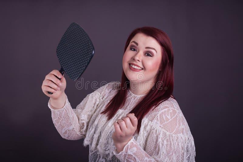 举行镜子美好的微笑的妇女 免版税图库摄影
