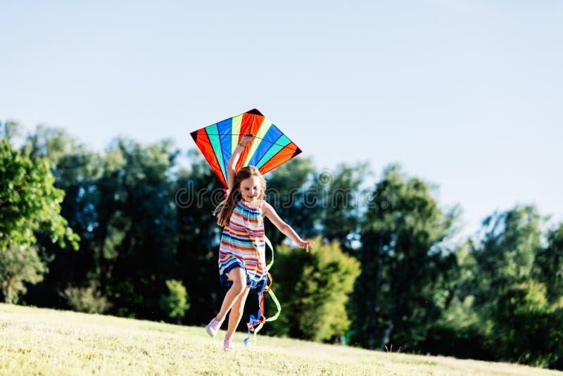 举行风筝和赛跑的愉快的小女孩 库存照片