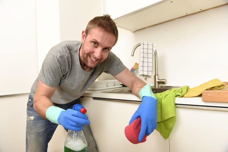 举行洗涤剂清洁浪花和海绵微笑的橡胶洗涤的手套的年轻愉快的人 免版税库存照片