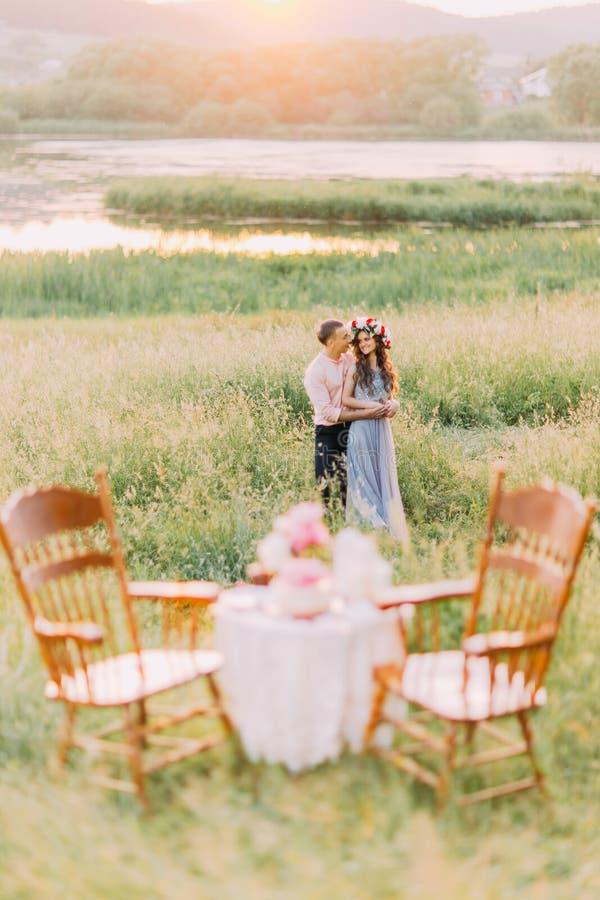 举行年轻的夫妇拥抱和在用蛋糕装饰的桌附近递,瓶,蜡烛,纺织品,在农村领域的桃红色花在 库存图片